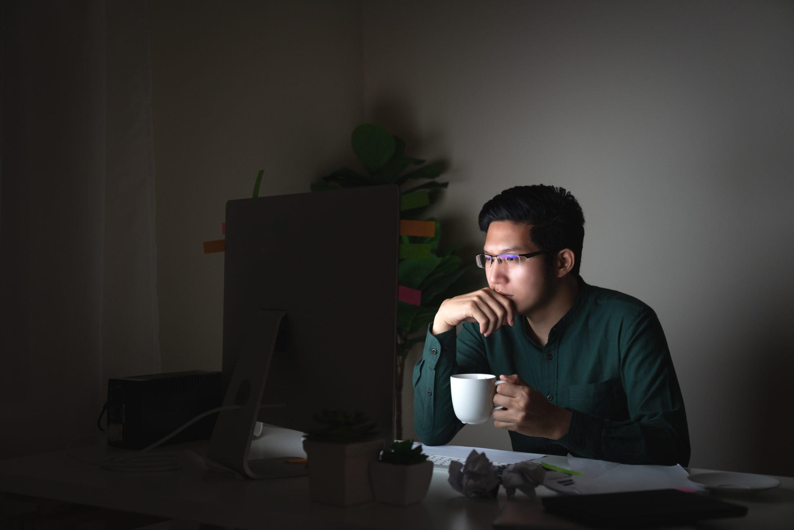 young man staring at a computer screen and holding a white coffee cup in a dark room