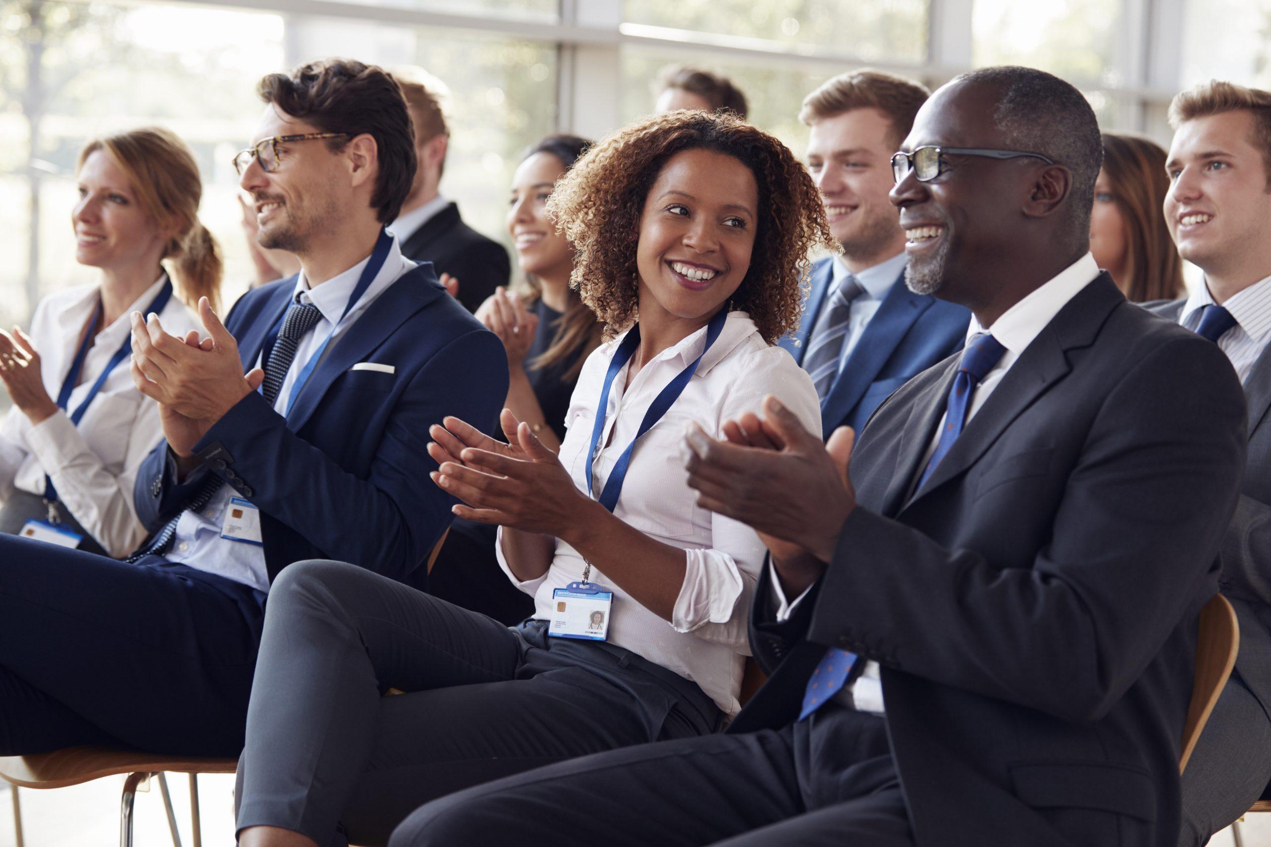 Smiling audience applauding at an attorneys seminar