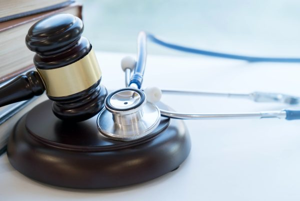 Gavel and stethoscope next to stack of large books